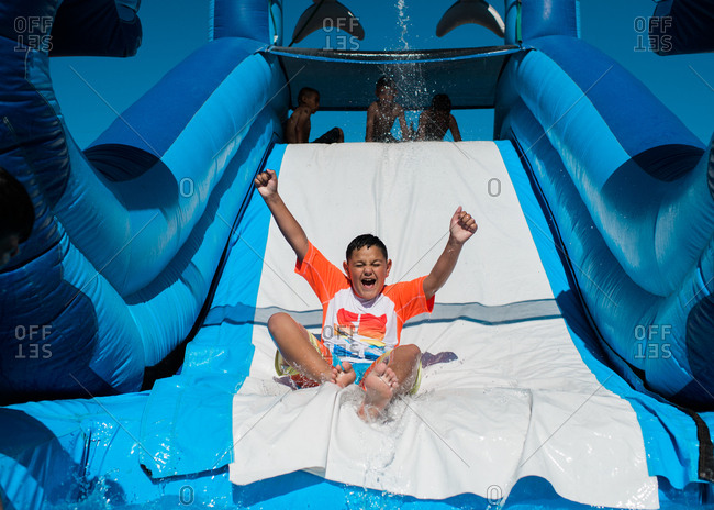 Excited boy going down water slide