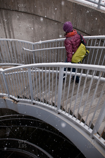 Woman climbing staircase in snow