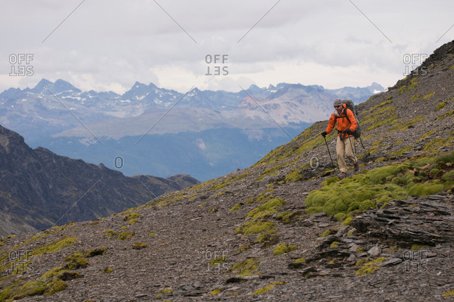 Hiker walking with sticks in rocky hills