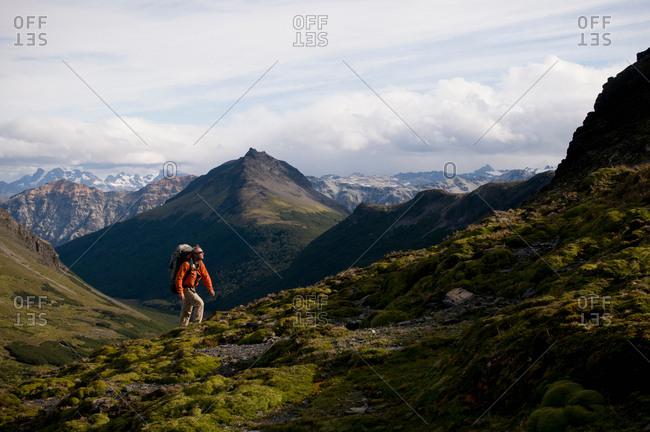 Hiker walking in grassy hills