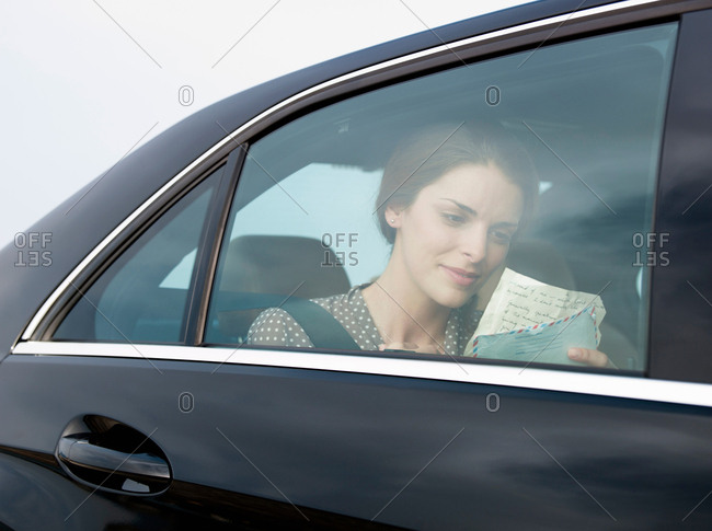 Woman holding letter in backseat of car