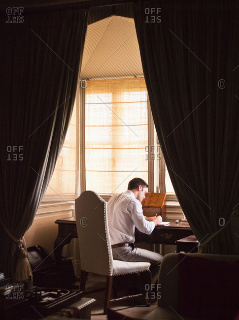 Businessman writing at desk in study