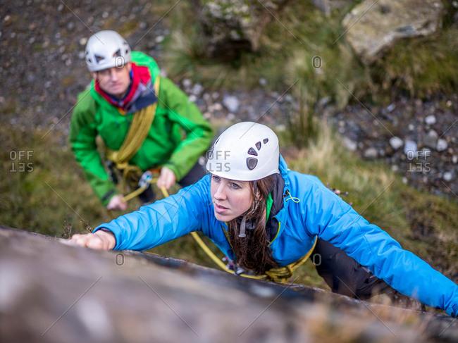 Rock climber scaling steep rock face
