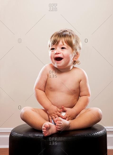 Toddler boy sitting on ottoman