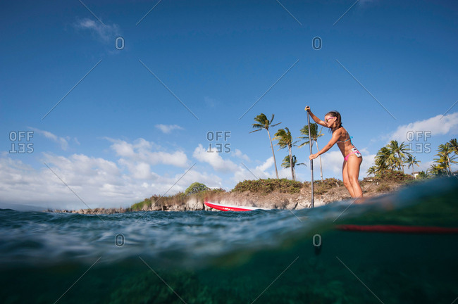 Woman paddle boarding on ocean