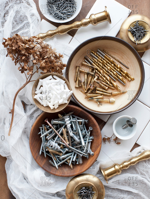 Still life of screws, nails and brass candlesticks