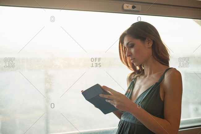 Young woman using digital tablet by window