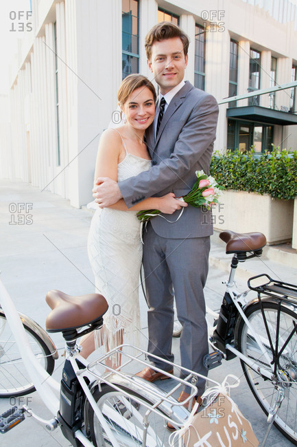 Portrait of young newlywed couple with bicycles
