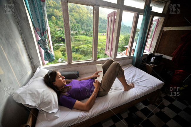 Woman relaxes in her room at a teahouse, Bhulbhule, Nepal