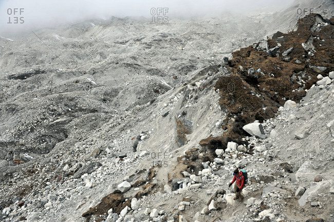 Female trekker descending across the moraine of the Nguzumpa Glacier, Nepal