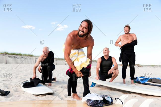 Four surfers getting dressed on beach