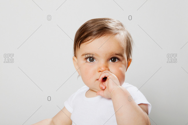 Baby boy looking at camera, hand covering mouth