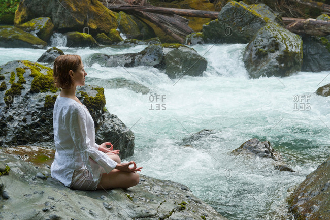 Woman meditating on rock by water