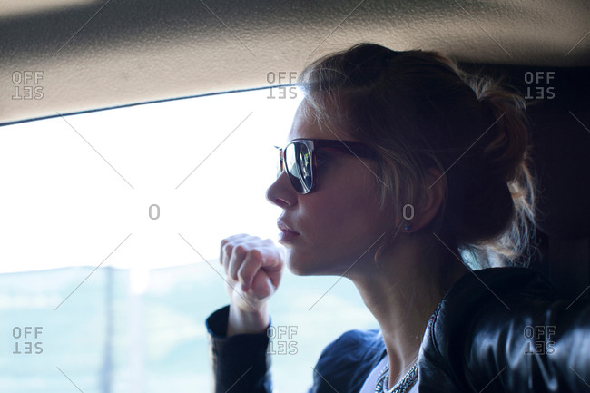 Woman in sunglasses, travelling in a car
