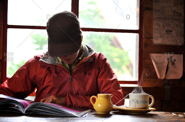 Women reads a magazine in a chocolateria, El Chalten, Argentina
