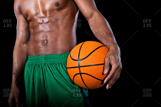 Mid section of basketball player with bare chest, holding ball