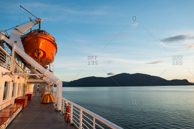 Warm orange sunlight bathes the ferry deck with dark mountains along the horizon