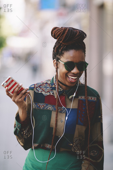 Happy young african american woman with phone on the street