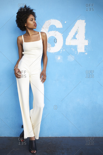 Trendy fearless young woman in a white jumpsuit looking away