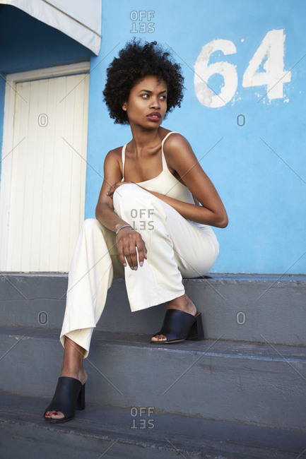 Trendy young woman sitting on steps looking away