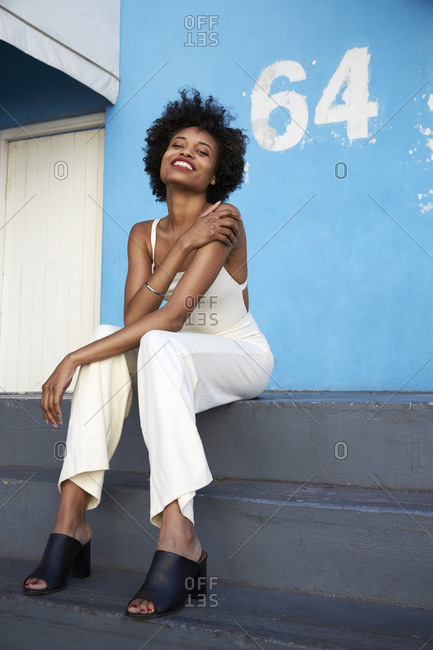 Trendy young woman sitting on steps smiling to camera