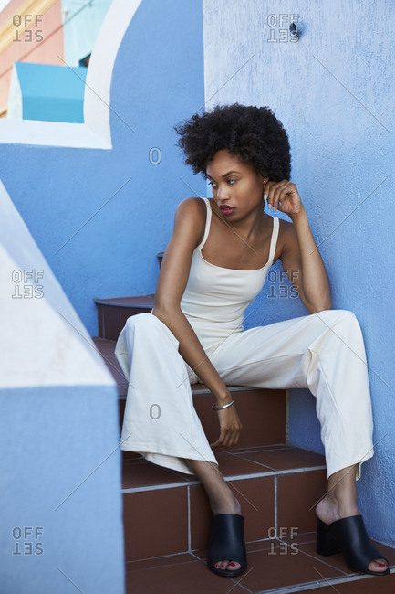 Chic young woman sitting on stairs looking away