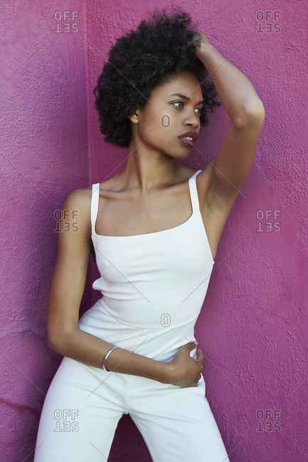 Trendy, strong young woman standing against pink wall