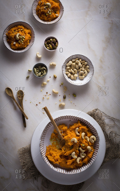 Carrot Halwa / Carrot pudding with nuts in a ceramic bowl on  on a marble table