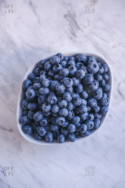 Fresh blueberries in a white bowl on white marble table