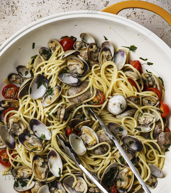 Vongole Shells Clams with tomato and parsley in cooking pan close-up