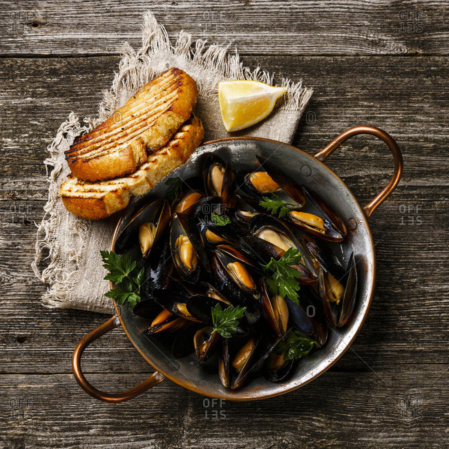 Mussels Clams in copper cooking dish pan and toasted bread on wooden background