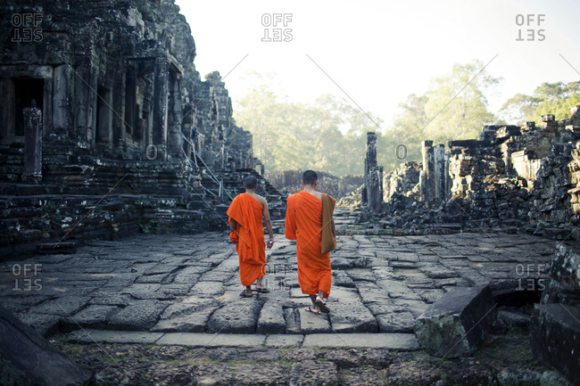 Angkor Thom, Cambodia - December 5, 2012. Two Buddhist Monks in their bright orange robes on their daily visit to Angkor Thom temple