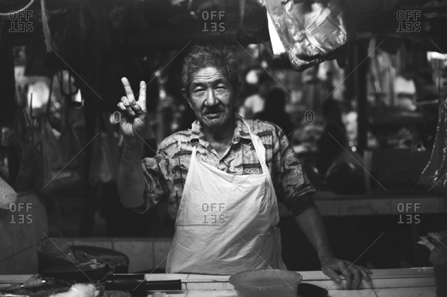Kuala Lumpur, Malaysia - July 29, 2010. A smiling butcher is showing the V sign at the local market in Kuala Lumpur