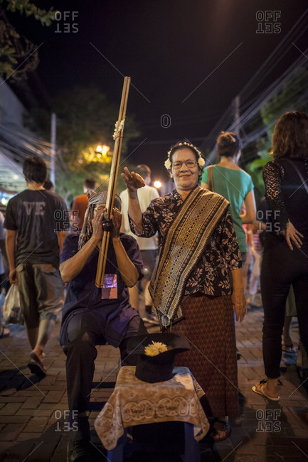 Chiang Mai, Thailand - November 4, 2011. A street musician is performing at the Sunday night market in Chiang Mai. The man is playing an instrument called ?Khene?, which is a mouth organ and usually made of bamboo