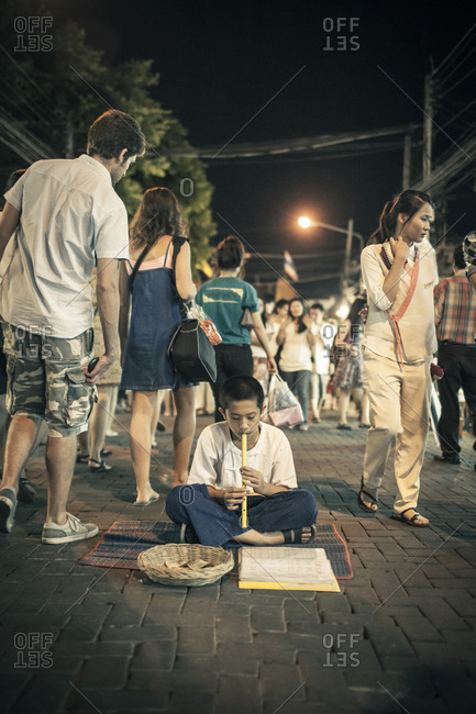 Chiang Mai, Thailand - November 4, 2011. A street musician is performing in a street of the Sunday night market in Chiang Mai. The kid is playing an instrument called ?Khlui?, which is a mouth organ and usually made of bamboo