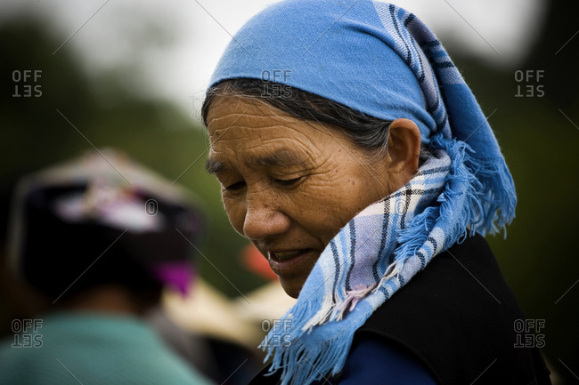 Yunnan, People's Republic of China - July 3, 2009. A smiling Chinese woman wears a headscarf at the local market