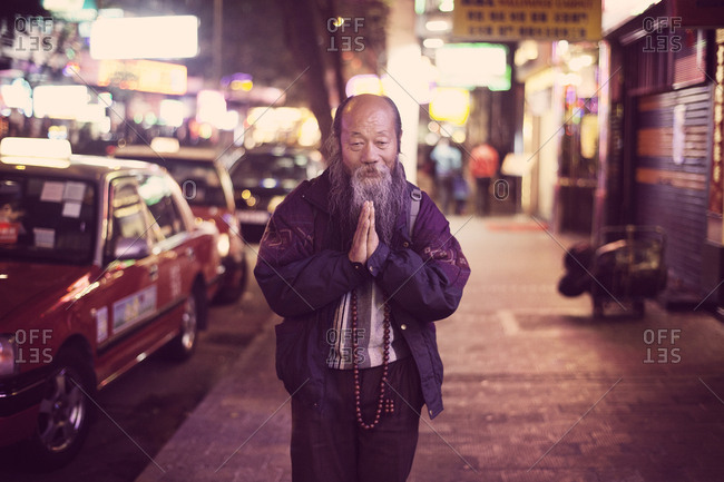 Hong Kong, People's Republic of China - February 5, 2011. A Buddhist Chinese man is doing the praying gesture on a street in Hong Kong