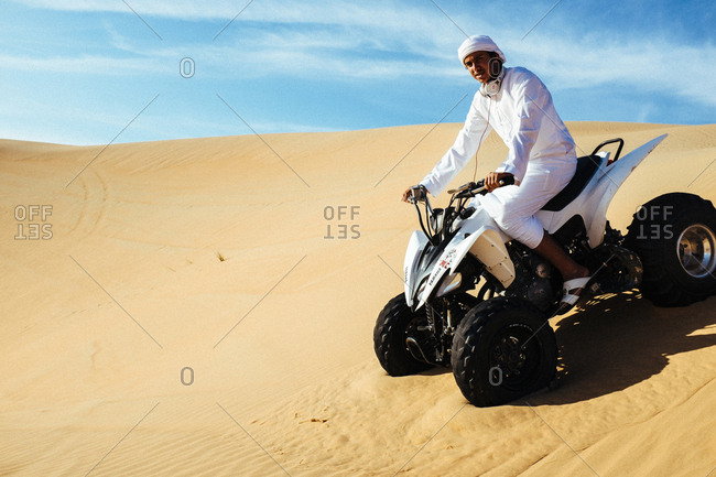 Dubai, United Arab Emirates - December 6, 2013. An Arabic man seen doing desert safari on a four wheeler in Dubai