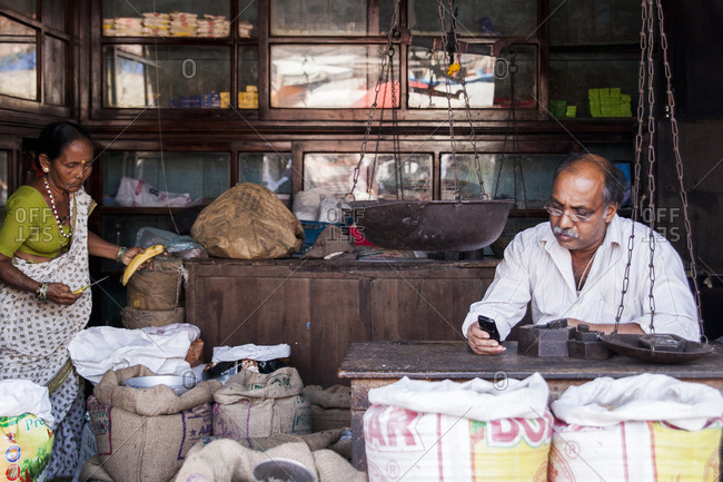 Mapusa, India - December 27, 2013. A shop keeper is selling goods at the Mapusa Market in North Goa