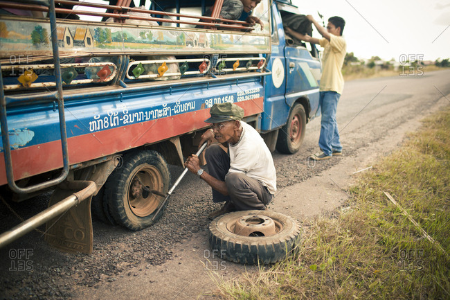 Si Phan Don, Laos - November 22, 2012. A bus driver is changing the wheel of a bus in Si Phan Don