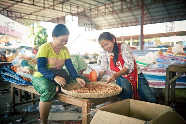 Si Phan Don, Laos - November 22, 2012. Two women are peeling peanuts at a local market in Laos