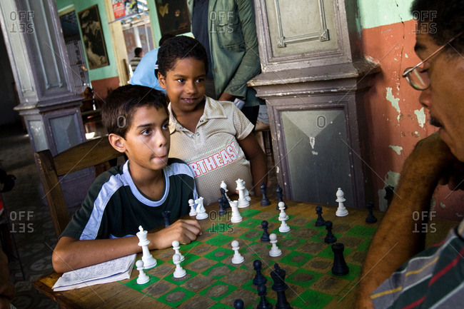 Havana, Republic of Cuba - August 6, 2008. A young chess player is competing with an adult player in a social club