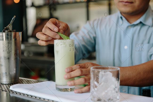 Bartender preparing a cocktail garnished with mint leaf