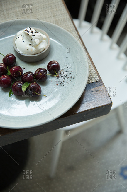 Cherries and mascarpone served on a ceramic plate