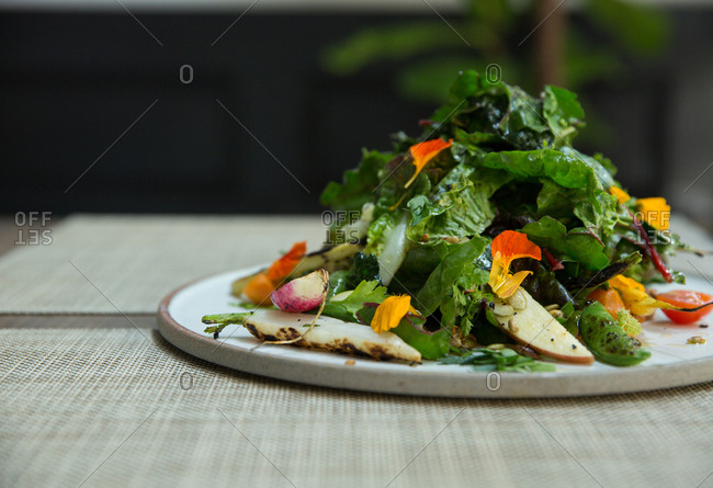 Large salad with leafy greens and roasted carrots