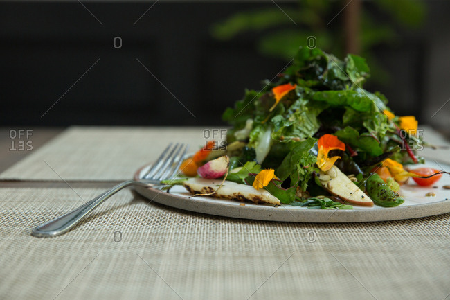 Salad with leafy greens, roasted carrots, and flower petals