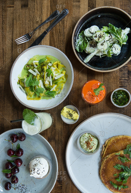 Brunch served with pasta dish, cucumber salad, pancakes, and cherries with mascarpone