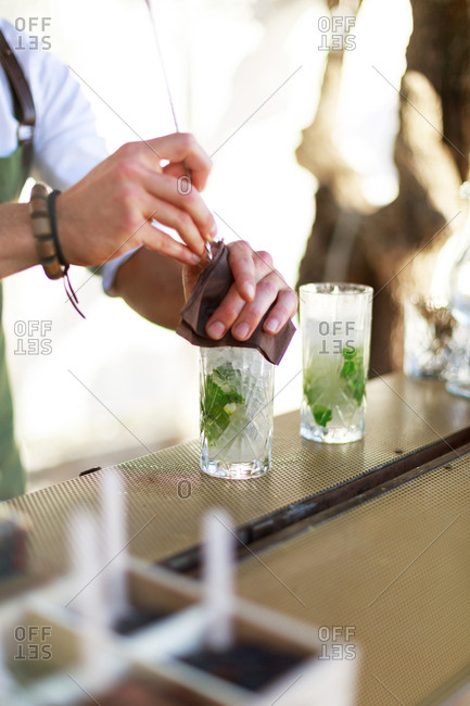Bartender mixing mint leaves into a cocktail outdoors