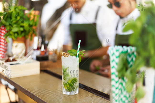 Cocktail with mint leaves and sliced fruit on an outdoor bar