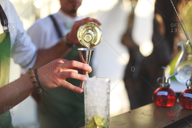 Bartender pouring liquor into a stainless steel jigger
